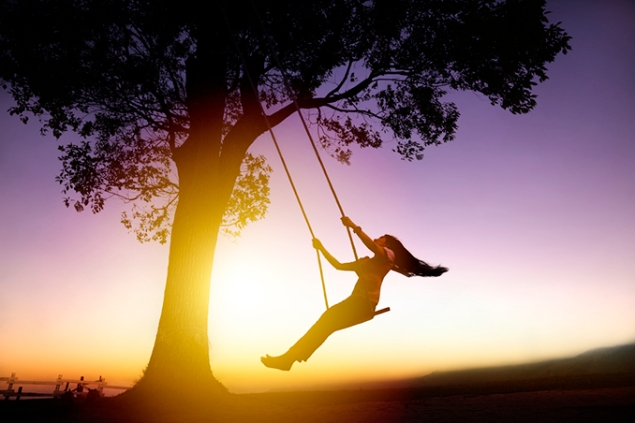 silhouette of happy young woman on a swing with sunset backgroun